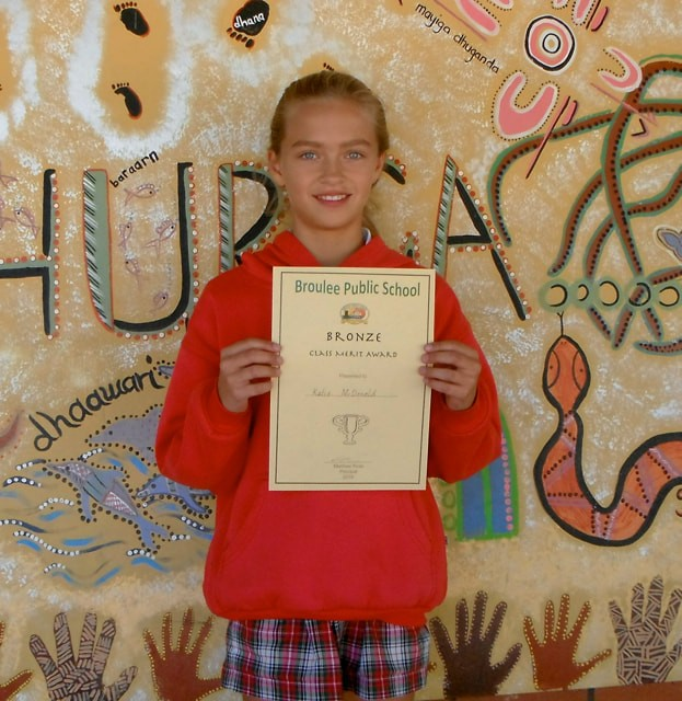 Katie McDonald posing with her Bronze class merit award certificate